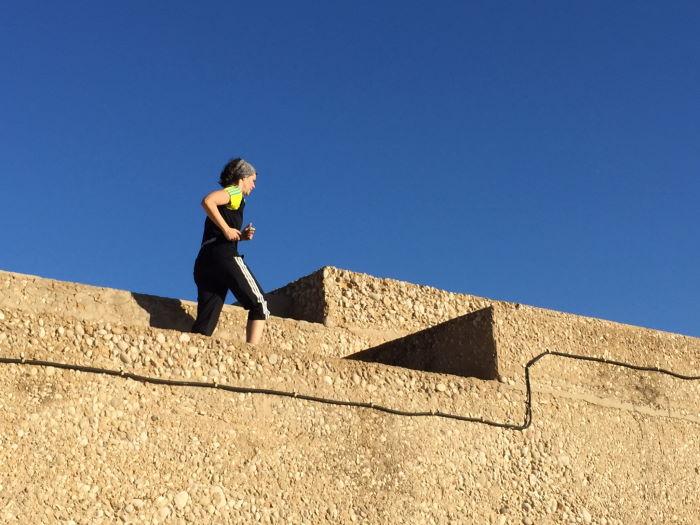 Frau rennt auf der Kaimauer